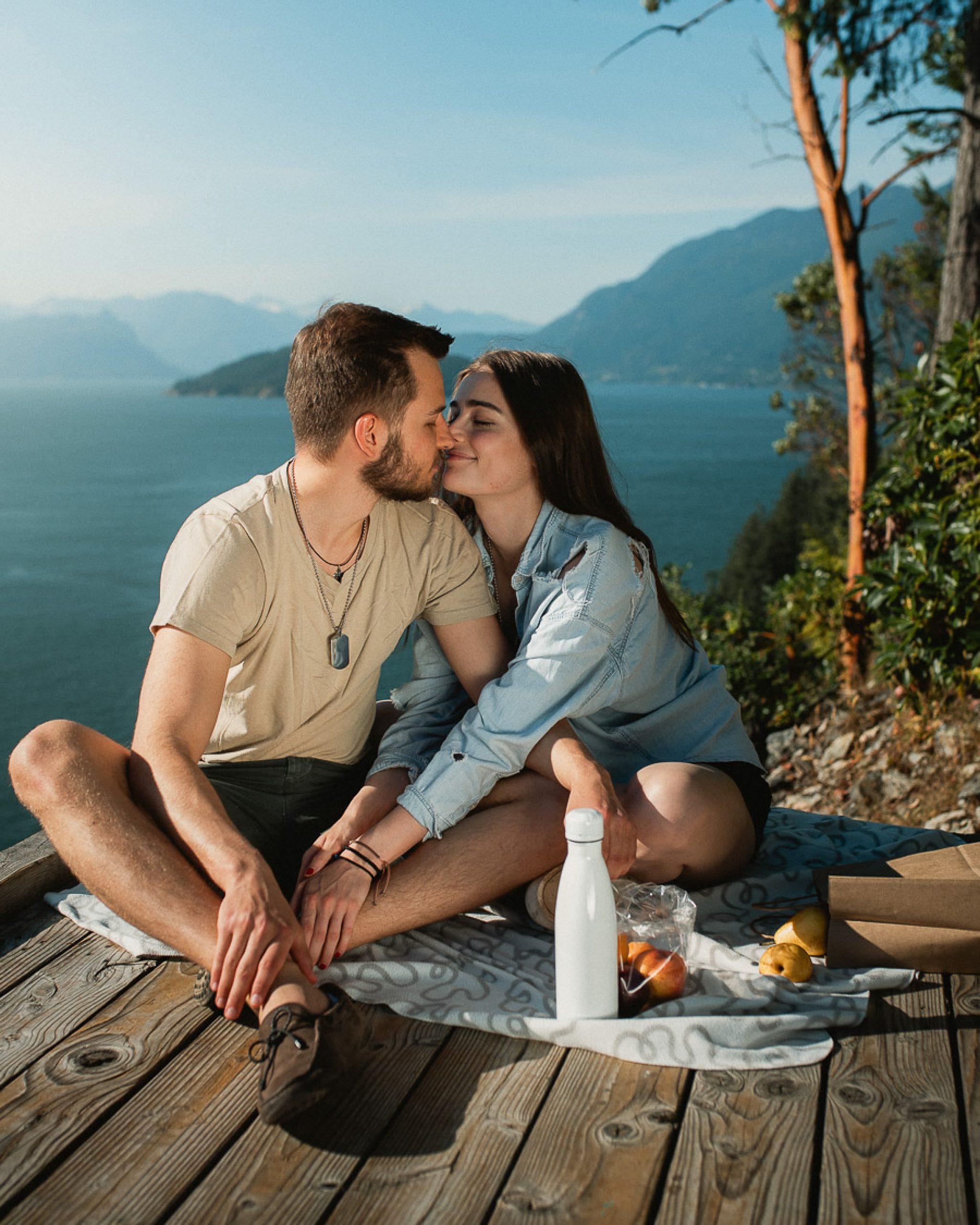 Couple kissing on lookout over water